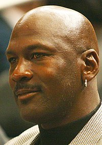 A smiling bald African American man wearing a silver earring and herringbone jacket