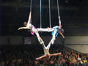 English: Young performers doing triple trapeze...