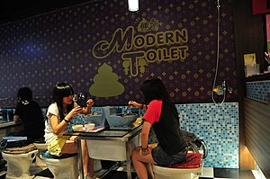 English: two persons eating at bathroom themed...