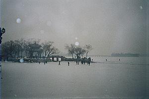 People walk across the frozen Kunming Lake whi...