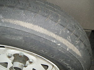 Tire showing wear in its sidewall (down to the...