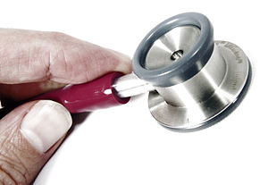 A stethoscope and partial hand.