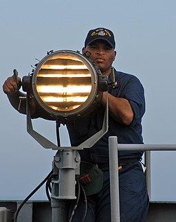Seaman sending Morse code signals