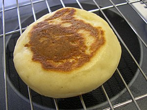An English muffin cooling on a rack.
