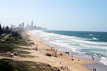 Pantai dengan kemiringan yang landai dari kawasan berumput di kiri ke arah laut di kanan, sebuah kota dapat dilihat di cakrawala