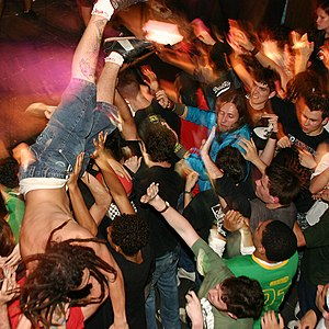 A man crowdsurfing in a moshpit, uploaded from...