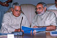 Modi and former Prime Minister Vajpayee looking at a blue-covered report