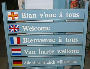 Multilingual welcome sign (Guernésiais on top)...