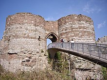 Two round towers of light yellow stone at the bottom and dark orangy stone at the top on either side of an arched entrance. A bridge leads from the entrance to allow access.