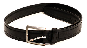 English: A worn, black leather belt with buckle.