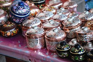 English: Small crafted copper containers on di...