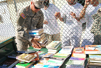 English: GUANTANAMO BAY, Cuba - A Joint Task Force Guantanamo Trooper displays reading materials from the JTF library for detainees to choose from Nov. 18, 2008. Detainees regularly choose from the library???s holdings of 8,000 books and magazines in English, Pashtu and Arabic. (JTF Guantanamo photo by Navy Petty Officer 2nd Class Patrick Thompson)