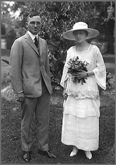 Wedding photo of man in gray suit and woman in hat with white dress holding flowers