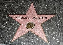 "A pink star with a gold colored rim and the writing ""Michael Jackson"" in its center. The star is indented into the ground and is surrounded by a marble colored floor."
