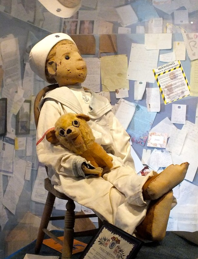 Doll in sailor suit seated on small chair; walls behind covered in pinned-up letters