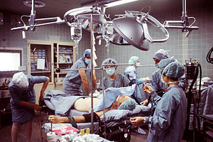 The image shows an operating room. A patient i...