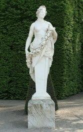 Pomone portant un diadème et tenant une guirlande de fruits et de fleurs sur sa poitrine, d'Étienne Le Hongre (jardins de Versailles).
