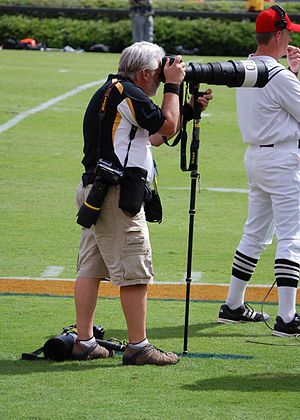 Sports photographer with multiple cameras and ...