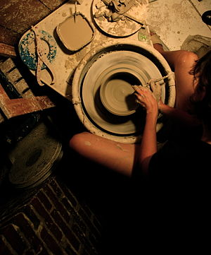 A potter creates a bowl on her electric-powere...