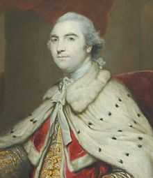 Half-length portrait of a man wearing furred robes and a white wig and looking regal. Underneath his white robes, he is wearing red and gold and he is sitting in a red chair.