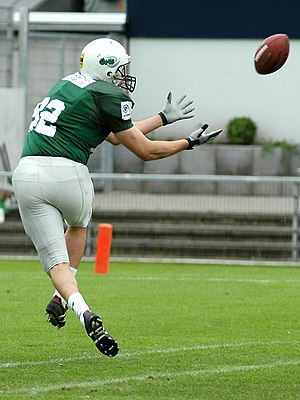 A Wide Receiver catching a ball.