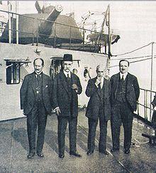 Quatre hommes en costume sur le pont d'un bateau.
