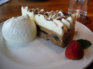 Slice of banoffee pie with vanilla ice cream a...