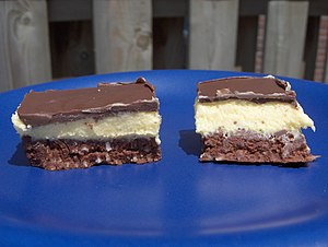 Two nanaimo bars on a blue plate