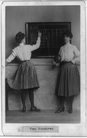 Two young women at blackboard, one holding bow...