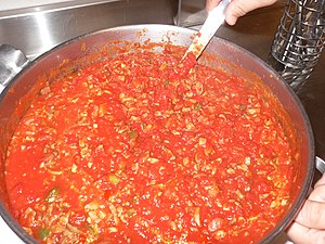 A pot of canned pasta sauce stirring on the stove.