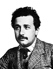 Head and shoulders shot of a young, moustached man with dark, curly hair wearing a plaid suit and vest, striped shirt, and a dark tie.