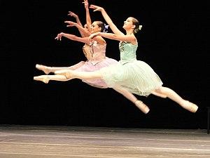 Three ballet dancers performing a grand jeté jump
