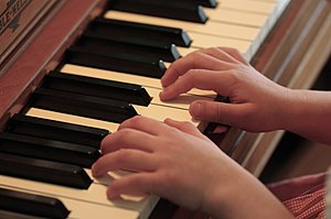 English: Child's hands resting on a piano keyboard