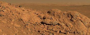 Fotografia tirada pelo rover Spirit a partir de um pequeno rochedo no meio da cratera Gusev que mostra a plan�cie interior da cratera e a respectiva parede ao fundo, no horizonte.