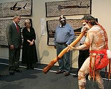 Pria Aborigin menampilkan Digeridoo indoors dengan 4 orang yang menonton, lukisan Aborigin dapat dilihat di tembok di belakangnya