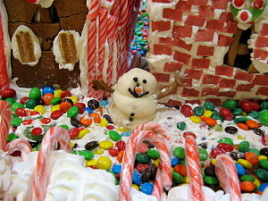 A squat candy snowman outside a gingerbread house.
