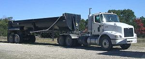 A rear dump trailer with a daycab tractor