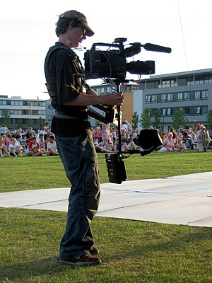 This photograph shows a man operating a steadicam