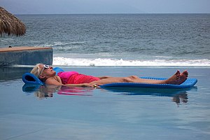 Mature lady sunbathing at swimming pool. Puert...