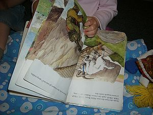 A child with an illustrated book of Three Bill...