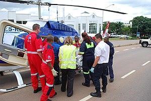 English: Paramedics load a patient into an air...