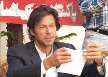 Khan tearing his nomination paper for National Assembly at a press conference; he boycotted the 2008 elections.