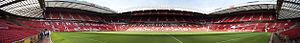 """Un stand d'un stade de football. Les sièges sont en rouge et les mots """"Manchester United"""" sont écrits en blanc. Le toit du stand est soutenu par une structure en porte-à-faux. Sur le rebord du toit, il est écrit """"Old Trafford Manchester""""."""