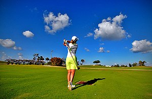 English: A female golfer takes a shot at a gol...