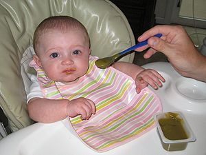 Baby eating baby food (blended green beans)