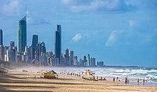 A beach populated by people; a city can be seen in the horizon
