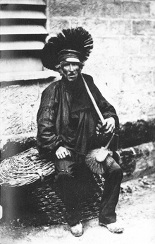 Chimney sweep in the 1850s, showing a middle-aged man sat outside a building on a lidded basket. He is wearing a dark boilersuit, his face is streaked in black. Over his shoulder is a pole ending in a circular brush head, on his knee is a long bristled hand brush