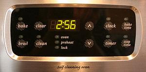 A digital clock built into an oven.