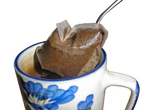 A tea bag being removed from a cup of tea