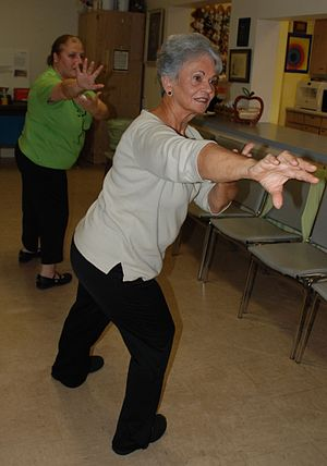 A Taoist Tai Chi class performing the move &qu...